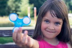 Young schoolgirl holding popular fidget spinner toy. Young schoolgirl holding popular fidget spinner toy - close up portrait royalty free stock image