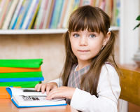 Young schoolgirl reading a book. looking at camera Royalty Free Stock Images