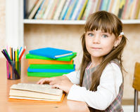 Young schoolgirl reading a book. looking at camera Stock Image