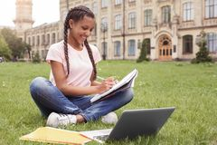Young schoolgirl at school yard sitting on lawn taking notes preparing for exam with laptop smiling happy royalty free stock photos