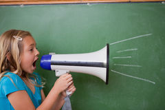Young schoolgirl screaming through a megaphone. In front of blackboard Stock Image
