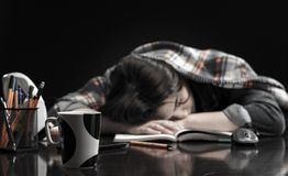 Young schoolgirl sitting at home  lying on desk royalty free stock images