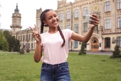 Young schoolgirl standing at school yard taking selfie on smartphone showing peace sign smiling cheerful stock photography