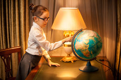Young schoolgirl studying globe at desk Royalty Free Stock Photography