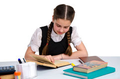 Young schoolgirl in unform studying. Horizontal portrait of young schoolgirl in unform studying isolated on white background Stock Photo