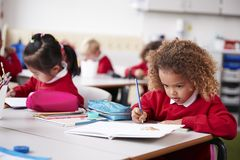 Young schoolgirl wearing school uniform sitting at a desk in an infant school classroom drawing, close up royalty free stock photography