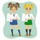 Young schoolgirls showing exam with good and bad test results Royalty Free Stock Photography