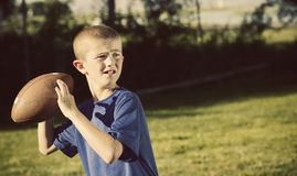 Young Schoolyard Quarterback. A determined young boy dreaming of one day being a star quarterback. Playing in his backyard. Vintage theme Stock Photography