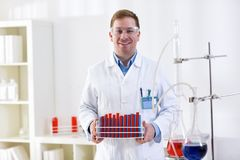 Young science holding tubes at professional lab. Young smiling science holding tubes at professional lab Stock Photos