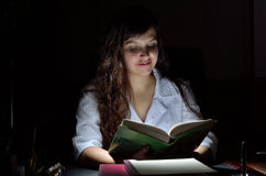 A young scientist with a book in the darkness Royalty Free Stock Photography