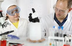 A young scientist conducts chemistry classes for a schoolgirl. Doing experiments with liquid nitrogen and dry ice in a chemical laboratory royalty free stock photo