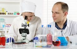 A young scientist conducts classes in biochemistry. With a little girl using a microscope in a chemical laboratory stock photos