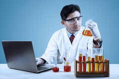 Young scientist doing experiment. With chemical fluid and laptop computer in laboratory Stock Image