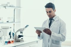 Young Scientist doing Research in Laboratory. Male Researcher wearing white Coat standing next to Microscope and Chemical Liquid Samples in Flasks looking at Royalty Free Stock Photos