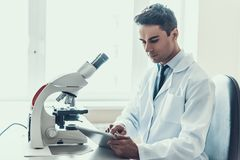 Young Scientist doing Research in Laboratory. Male Researcher wearing white Coat sitting at Desk next to Microscope looking at Tablet in Laboratory. Scientist Stock Image