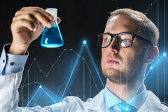 Young scientist holding test flask with chemical. Science, chemistry, research and people concept - young scientist holding test flask with chemical and diagram Stock Photo
