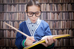Young scientist, hustler with glasses in the library, with a hug. Funny young scientist, hustler with glasses in a library,education concept Royalty Free Stock Photo
