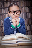 Young scientist, hustler with glasses in the library, learn from. Boy in library with glasses learning from books Stock Photo