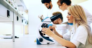 Young scientist looking through microscope in laboratory stock image