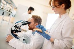 Young scientist looking through microscope in laboratory. Young male scientist looking through microscope in laboratory Stock Image