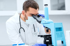 Young scientist looking to microscope in lab. Science, medicine, technology, biology and people concept - young male scientist with test tubes looking to Royalty Free Stock Photography
