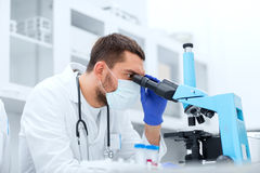 Young scientist looking to microscope in lab. Science, medicine, technology, biology and people concept - young male scientist with test tubes looking to Royalty Free Stock Images