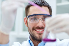 Young scientist making test or research in lab. Science, chemistry, technology, biology and people concept - young scientist mixing reagents from glass flasks Royalty Free Stock Images