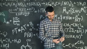 Young scientist man clean his glasses in chemical and mathematical equations wall room interior. Young scientist man posing in chemical and mathematical stock video