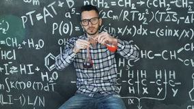 Young scientist man make laboratory experiment in chemical and mathematical equations wall room. Young scientist man posing in chemical and mathematical stock video