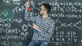 Young scientist man make laboratory experiment in chemical and mathematical equations wall room. Young scientist man posing in chemical and mathematical stock video footage
