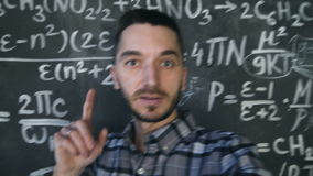 Young scientist man making selfie shoot in chemical and mathematical equations wall room interior. Young scientist man posing in chemical and mathematical stock video footage