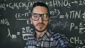 Young scientist man making selfie shoot in chemical and mathematical equations wall room interior. Young scientist man posing in chemical and mathematical stock video