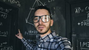 Young scientist man making selfie shoot in chemical and mathematical equations wall room interior. Young scientist man posing in chemical and mathematical stock footage