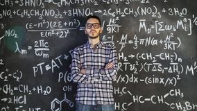 Young scientist man posing in chemical and mathematical equations wall room interior. Background Stock Photo