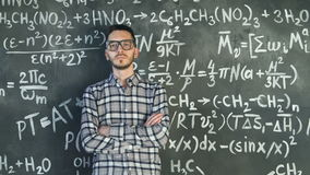 Young scientist man posing in chemical and mathematical equations wall room interior. Background stock footage
