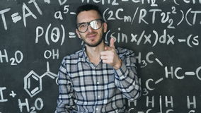 Young scientist man posing in chemical and mathematical equations wall room interior. Background stock video footage