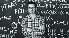 Young scientist man in laboratory with chemical and mathematical equations wall room. Young scientist man posing in chemical and mathematical equations wall room Stock Image