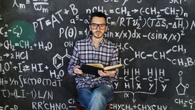 Young scientist man read book in chemical and mathematical equations wall room interior. Young scientist man posing in chemical and mathematical equations wall Royalty Free Stock Images