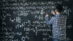 Young scientist man write chock in chemical and mathematical equations wall room interior. Young scientist man posing in chemical and mathematical equations wall Stock Photo