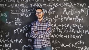 Young scientist man posing in chemical and mathematical equations wall room interior. Background Stock Image