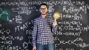 Young scientist man posing in chemical and mathematical equations wall room interior. Background Stock Photography