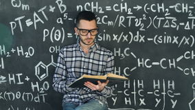 Young scientist man read book in chemical and mathematical equations wall room interior. Young scientist man posing in chemical and mathematical equations wall stock video footage