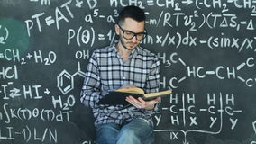 Young scientist man read book in chemical and mathematical equations wall room interior. Young scientist man posing in chemical and mathematical equations wall stock footage