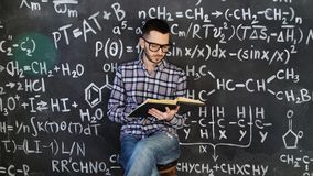 Young scientist man read book in chemical and mathematical equations wall room interior. Young scientist man posing in chemical and mathematical equations wall Royalty Free Stock Photo