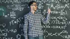 Young scientist man stand with lamp in chemical and mathematical equations wall room interior. Young scientist man posing in chemical and mathematical equations stock video footage
