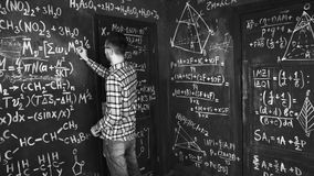 Young scientist man write chock in chemical and mathematical equations wall room interior. Young scientist man posing in chemical and mathematical equations wall Royalty Free Stock Photos