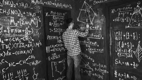 Young scientist man write chock in chemical and mathematical equations wall room interior. Young scientist man posing in chemical and mathematical equations wall Royalty Free Stock Photography