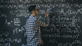 Young scientist man write chock in chemical and mathematical equations wall room interior. Young scientist man posing in chemical and mathematical equations wall stock footage