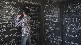 Young scientist man write chock in chemical and mathematical equations wall room interior timelapse. Young scientist man posing in chemical and mathematical stock video