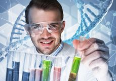 Young scientist mixing reagents in glass flask in clinical laboratory. Handsome scientist making research over dna molecule structure Royalty Free Stock Images